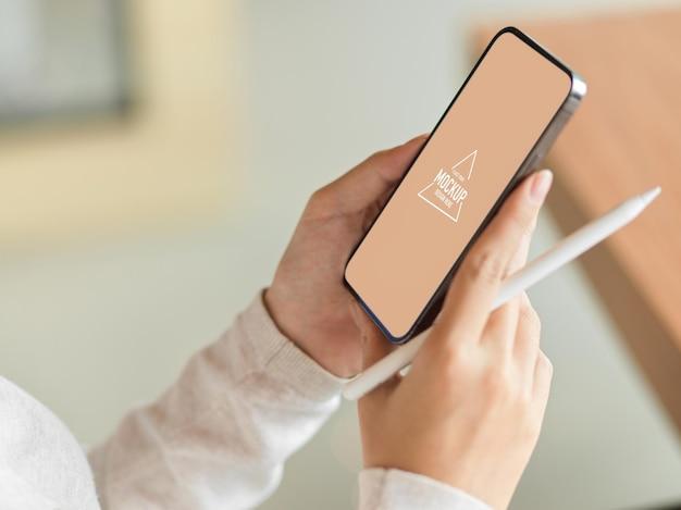 Makieta smartfona na kobiece dłonie, trzymająca rysik i rozmyte tło