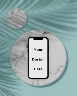 Makieta smartfona na marmurowej teksturze z renderowania 3d cień tropikalnego drzewa