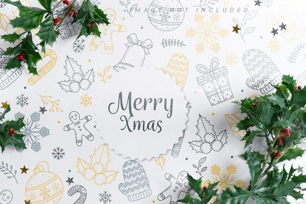 Makieta świąteczna ramka ozdobiona świątecznymi liśćmi ostrokrzewu.