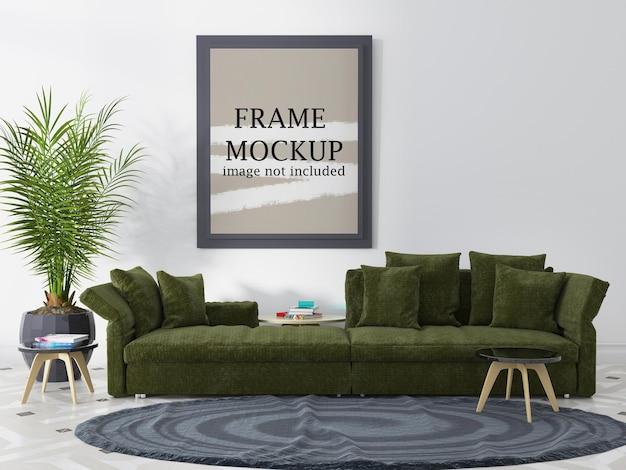 Makieta szarej ramki nad zieloną sofą