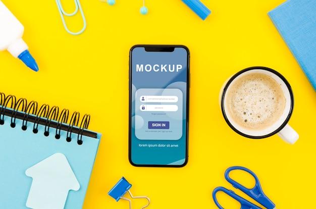 Makieta telefonu leżącego na płasko z kawą na biurku