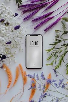 Makieta telefonu oprawione w kilka suszonych kolorowych kwiatów