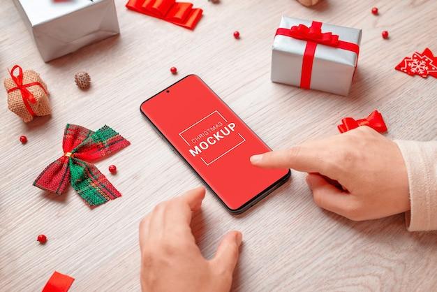 Makieta telefonu otoczona dekoracjami świątecznymi i prezentami