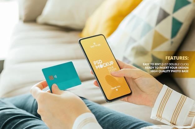 Makieta telefonu trzymana przez nowoczesną kobietę z kartą kredytową siedzącą na kanapie