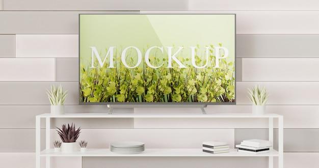 Makieta telewizora zamontowana na ścianie z płytek z białym stołem