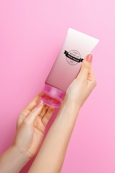 Makieta tubki kremu w rękach na różowej przestrzeni