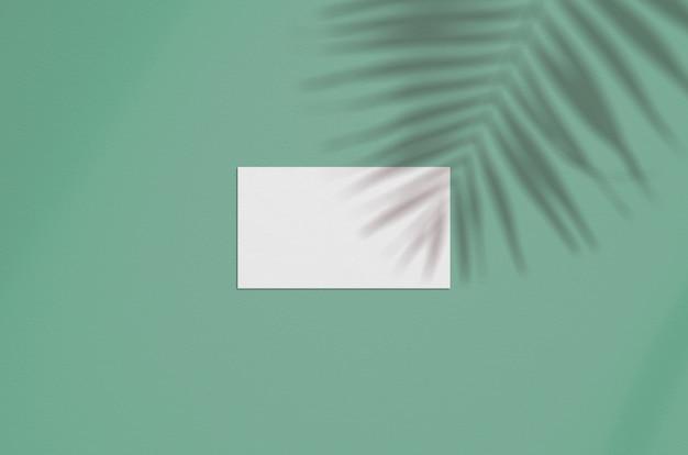 Makieta wizytówki. naturalne oświetlenie nakładkowe ocienia liście palmowe
