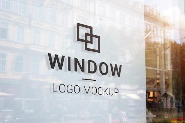 Makieta z czarnym logo na oknie sklepu z białym wnętrzem. nowoczesne okno sklepowe w centrum miasta. budynki i słońce odbijają światło