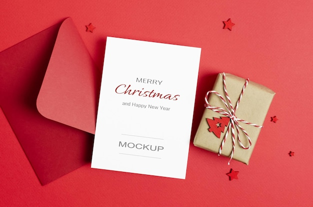 Makieta z życzeniami bożonarodzeniowymi lub zaproszeniem z kopertą i ozdobnym pudełkiem na czerwono