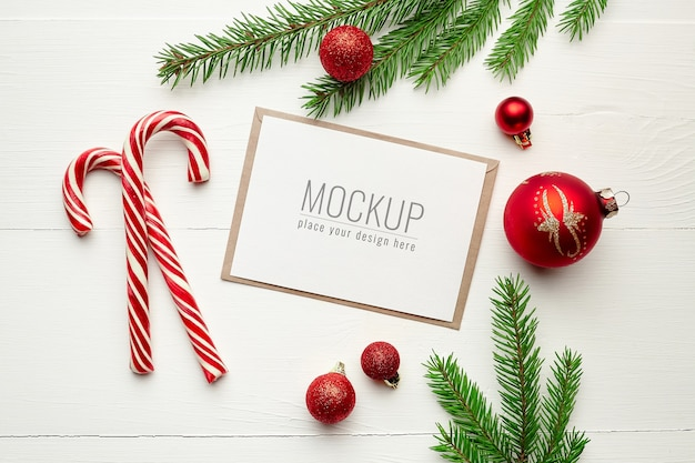 Makieta z życzeniami z cukierkami, dekoracjami świątecznymi i gałęziami jodły