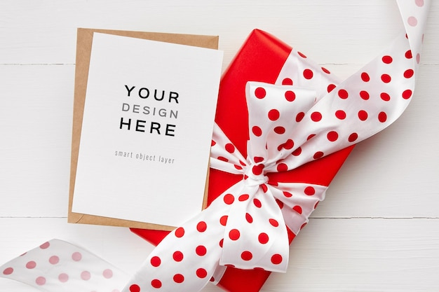 Makieta z życzeniami z czerwonym pudełkiem z kokardą na białym tle