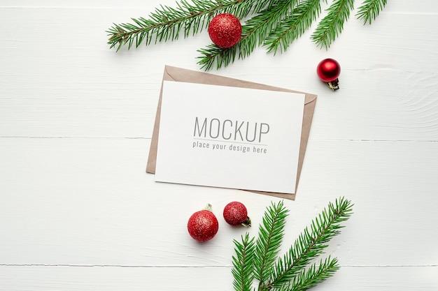 Makieta z życzeniami z dekoracjami świątecznymi i gałęziami jodły