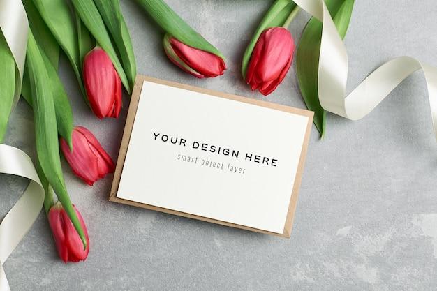 Makieta z życzeniami z kopertą i czerwonymi kwiatami tulipanów