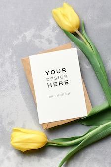 Makieta z życzeniami z kopertą i żółtymi kwiatami tulipanów na szaro