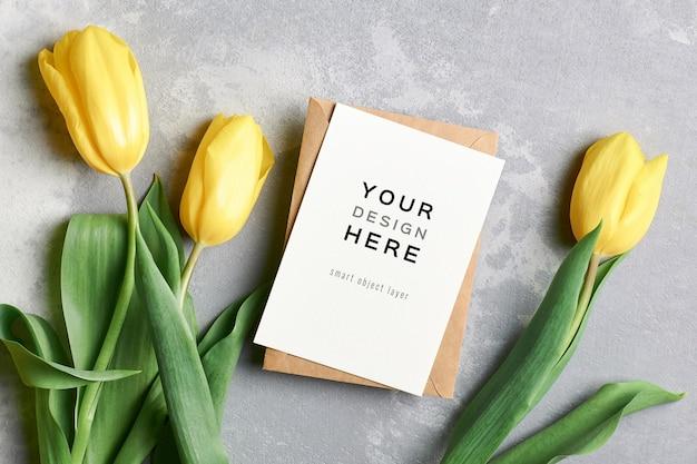 Makieta z życzeniami z kopertą i żółtymi kwiatami tulipanów