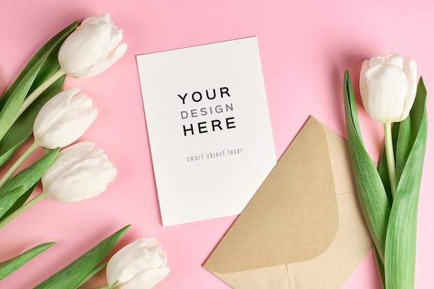 Makieta z życzeniami z koperty i białych kwiatów tulipanów na różowym tle