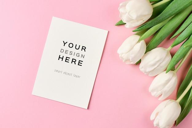 Makieta z życzeniami z koperty i białych kwiatów tulipanów