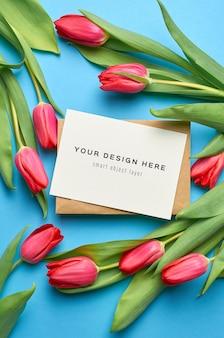 Makieta z życzeniami z koperty i bukietem czerwonych tulipanów na niebieskim tle