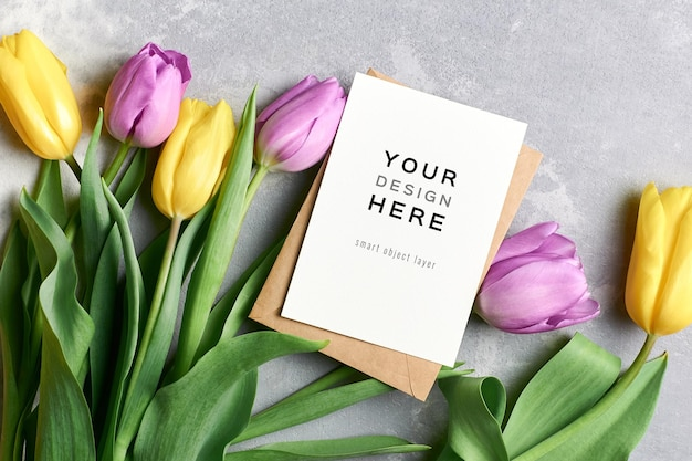Makieta z życzeniami z koperty i żółtych i fioletowych kwiatów tulipanów