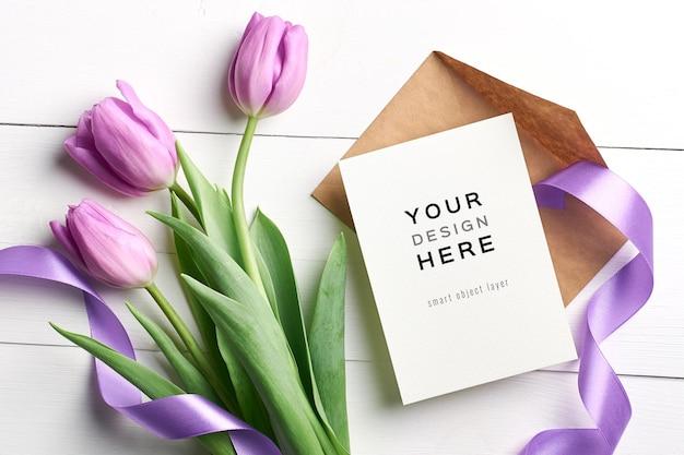 Makieta z życzeniami z kwiatów tulipanów, koperty i wstążki na podłoże drewniane