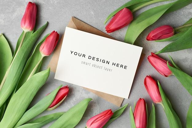 Makieta z życzeniami z okazji dnia kobiet z kopertą i czerwonymi kwiatami tulipanów