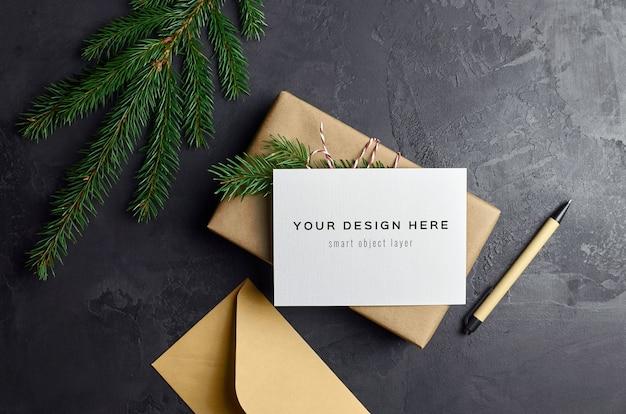 Makieta z życzeniami z pudełkiem na prezent świąteczny i gałęziami jodły w ciemności