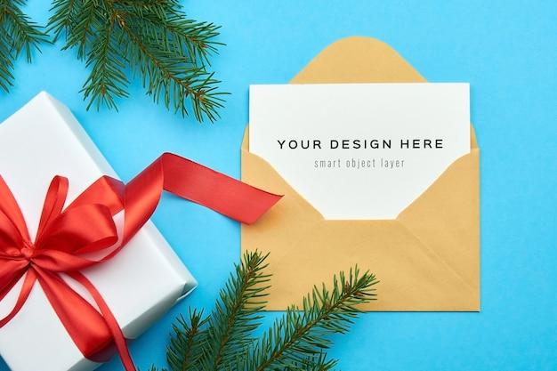 Makieta z życzeniami z pudełkiem na prezent świąteczny i gałęziami jodły