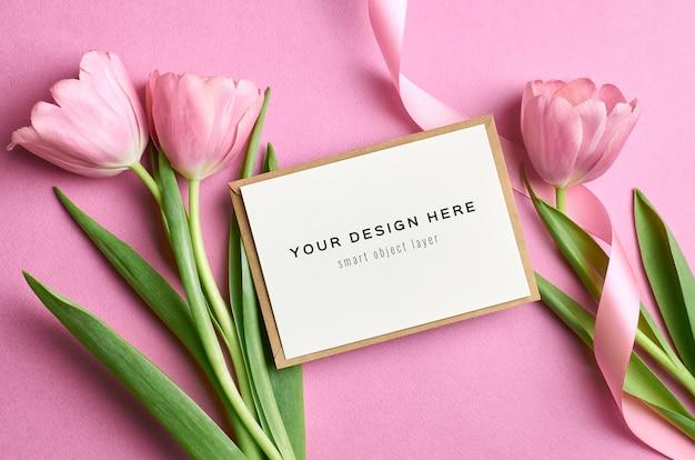 Makieta z życzeniami z różową kopertą i bukietem kwiatów tulipanów