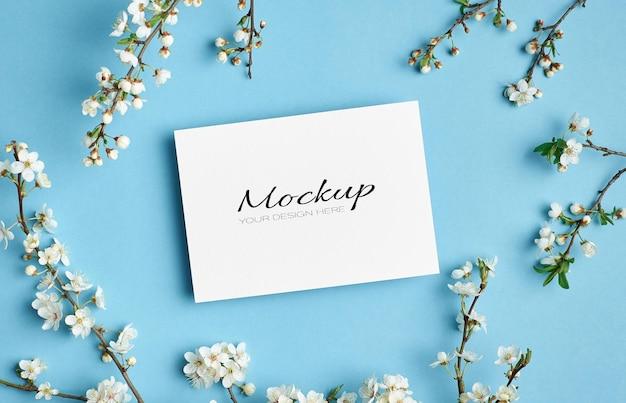 Makieta zaproszenia lub karty z pozdrowieniami z gałązek wiosennych kwiatów wiśni na niebiesko