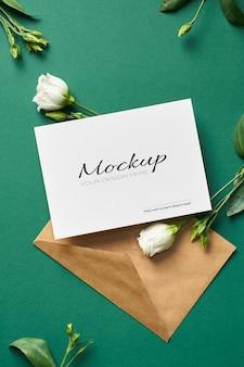 Makieta zaproszenia lub karty z pozdrowieniami z kopertą i białymi kwiatami eustoma na zielono