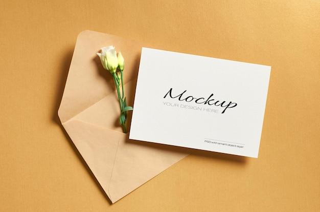 Makieta zaproszenia lub karty z pozdrowieniami z kopertą i białymi kwiatami eustoma