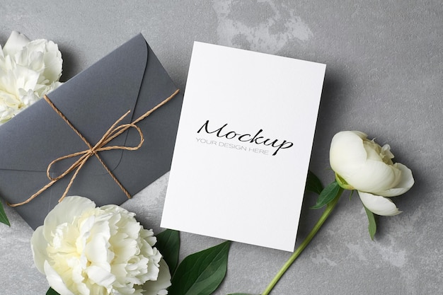 Makieta zaproszenia lub karty z pozdrowieniami z kopertą i białymi kwiatami piwonii na szaro