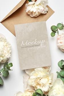 Makieta zaproszenia lub karty z pozdrowieniami z kopertą i białymi kwiatami piwonii z gałązkami eukaliptusa