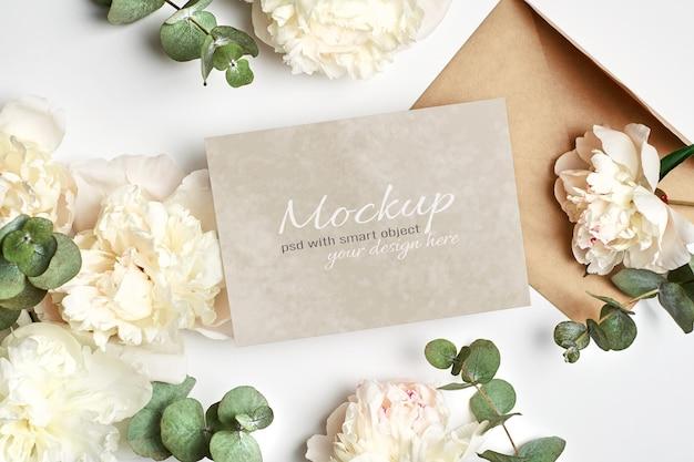 Makieta zaproszenia lub karty z pozdrowieniami z kopertą i białymi kwiatami piwonii