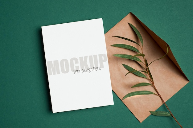 Makieta zaproszenia lub karty z pozdrowieniami z kopertą i gałązką eukaliptusa na zielono
