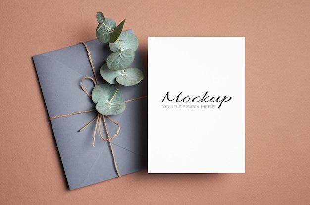 Makieta zaproszenia lub karty z pozdrowieniami z kopertą i gałązką eukaliptusa
