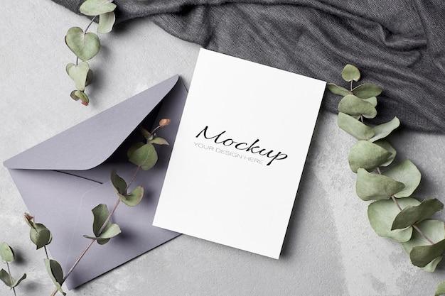 Makieta zaproszenia lub karty z pozdrowieniami z kopertą i gałązkami eukaliptusa
