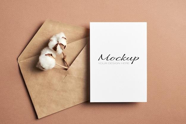 Makieta zaproszenia lub karty z pozdrowieniami z kopertą i naturalnymi kwiatami bawełny na beżu