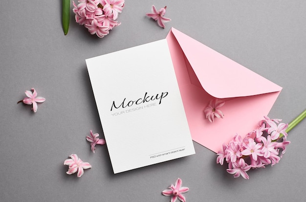 Makieta zaproszenia lub karty z pozdrowieniami z kopertą i różowymi hiacyntowymi kwiatami