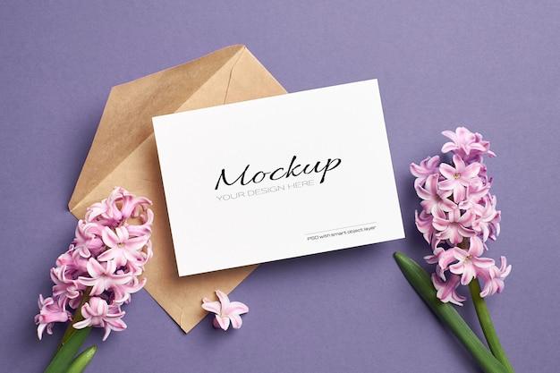 Makieta zaproszenia lub karty z pozdrowieniami z kopertą i różowymi kwiatami hiacyntu