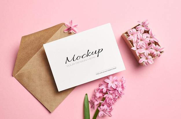 Makieta zaproszenia lub karty z pozdrowieniami z kopertą i różowymi kwiatami w pudełku