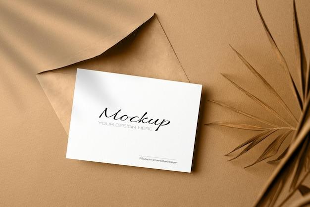 Makieta zaproszenia lub karty z pozdrowieniami z kopertą i suchym liściem palmowym