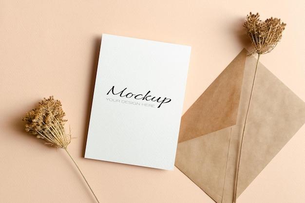 Makieta zaproszenia lub karty z pozdrowieniami z kopertą i suchymi dekoracjami roślinnymi
