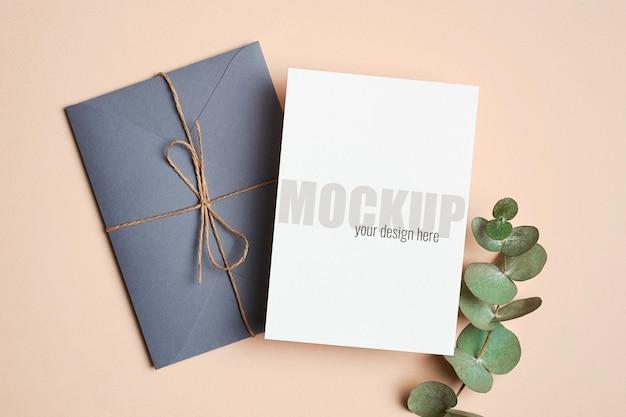 Makieta zaproszenia lub karty z pozdrowieniami z kopertą i zieloną gałązką eukaliptusa