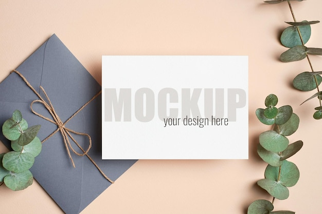 Makieta zaproszenia lub karty z pozdrowieniami z kopertą i zielonymi gałązkami eukaliptusa