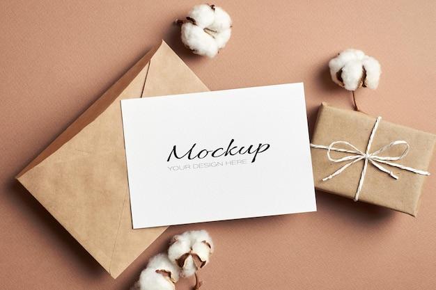 Makieta zaproszenia lub karty z pozdrowieniami z kopertą, pudełkiem prezentowym i kwiatami naturalnej bawełny