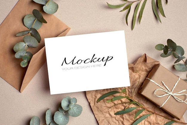 Makieta zaproszenia lub karty z pozdrowieniami z kopertą, pudełkiem prezentowym i zielonymi gałązkami eukaliptusa