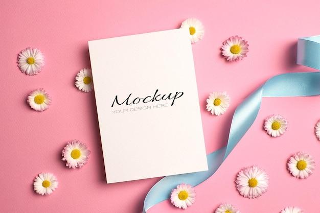 Makieta zaproszenia lub karty z pozdrowieniami z kwiatami wstążki i stokrotki na różowo