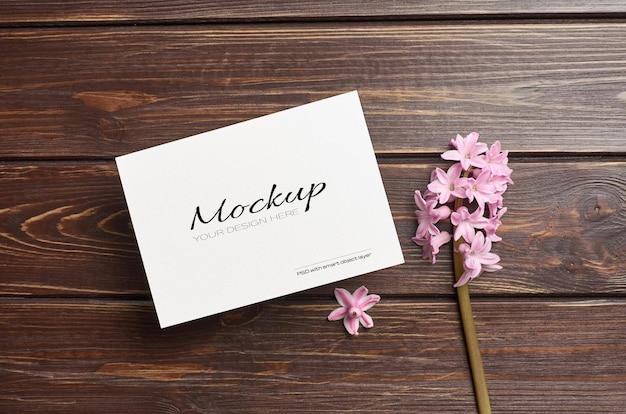 Makieta zaproszenia lub karty z pozdrowieniami z kwiatem hiacyntowym na drewnianym