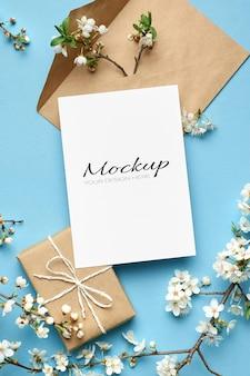 Makieta zaproszenia lub karty z pozdrowieniami z pudełkiem prezentowym, kopertą i gałązkami wiśni z kwiatami na niebiesko